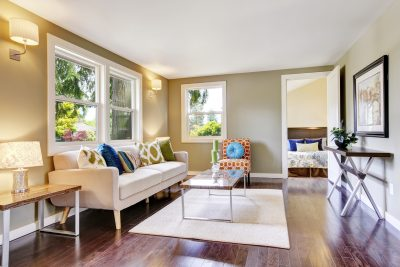A bright and colorful living room area, with two white hung windows on the back wall.