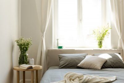 Sunny natural style bedroom interior with a bed in the middle, gray linen and pillows, and a vanilla blanket. A lamp and a stool with fresh flowers next to the bed. Big window in the back.