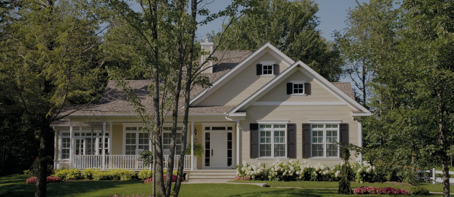Beige farm house with dark shutters and greenery